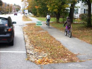 gorham-2-students-bike-through-village-on-sidewalk-sarah-cushman